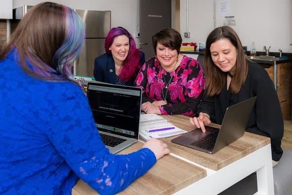 Grupo de quatro mulheres discutindo um projeto e se divertindo